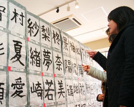 自分の作品を見つけて喜ぶ家族連れ=金沢市の 「金沢ふるさと偉人館」(昨年の「名前一文字展」)