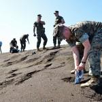 式典後、南海岸で砂を袋に詰める米海兵隊員ら =19日午後、東京都小笠原村