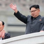 10日、平壌の金日成広場で行われたパレードで、手を振る北朝鮮の金正恩労働党委員長(右)。左は金永南最高人民会議常任委員長(時事)