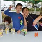 カメラに向かって無邪気にピースサインをする子供たち =25日午後、熊本県の益城町総合体育館