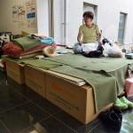 段ボールのベッドで休む女性。立ち上がる際に楽だと評判も良い =25日午後、熊本県の益城町総合体育館