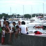 海辺で暮らす路上生活者たちの背後には高級ヨットハーバー。格差のコントラスト