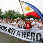 「マルコスは英雄ではない」の横断幕を広げ埋葬に反対する参会者たち