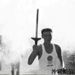 TOKYO1964のロゴマークのゼッケンを着けて走る聖火ランナー