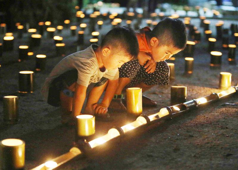 77人の犠牲者をしのび、鎮魂の竹灯籠に祈り込め