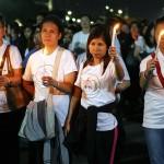 ロウソクを灯して行進する参加者たち