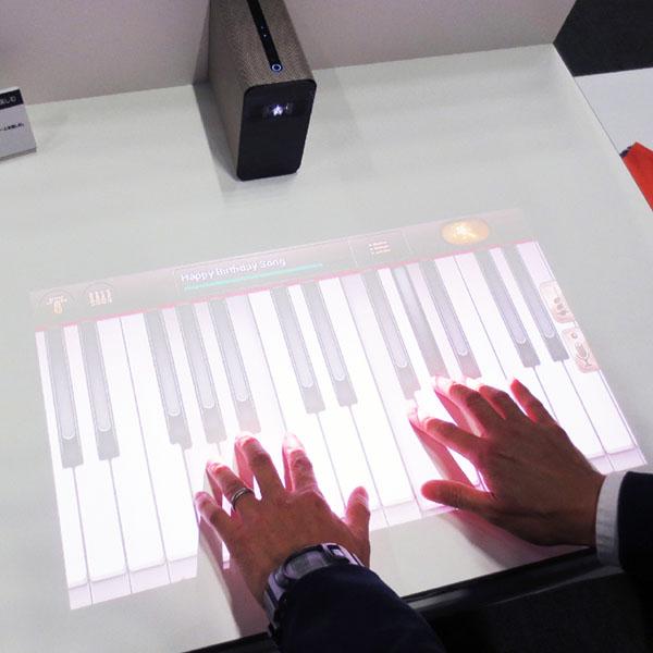 壁やテーブルに投写した映像にタッチして操作
