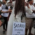 貞子のコスプレで抗議する参会者