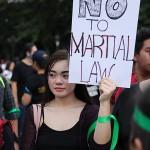 プラカードを掲げ戒厳令に反対する女性