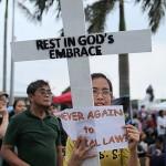 十字架を模ったプラカードで戒厳令に反対する女性