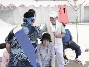 地域のイベントで有権者と握手する候補者(15日、沖縄県那覇市)