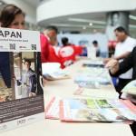 日本旅行に関するパンフレットを求める人々