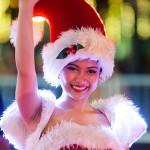 クリスマスパレードで愛嬌をふりまくサンタコスチュームの女性