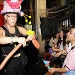 風船で香港人の観客にハートマークをつくるマジシャン