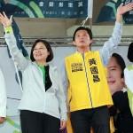 12月13日、台湾の新北市汐止駅前で蔡英文民進党主席(左端)と一緒に壇上で手を振るミニ政党「時代力量」の黄国昌党主席