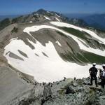 内蔵助カールに残る雪渓を見ながら、山を下る富山県内の中学生たち