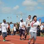 軍人のボランティアのエスコートを受けながら全力疾走する参加者