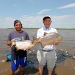 レダ敷地内のパラグアイ川支流を背景に大きく育ったパクーを抱える中田実氏(右)と先住民の青年