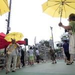 雨傘革命運動のシンボルである黄色い傘を開いて演説を聞く人々も