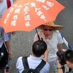 香港で真の普通選挙を求める内容を傘に書き込んで主張する人