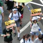 真の普通選挙実現を求めるプラカードを持ってデモ行進する人々