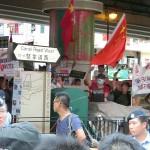 民主化デモの行進ルート近くで親中派が五星紅旗を振りながら抗議する人々。デモ参加者から激しいブーイングが続いた