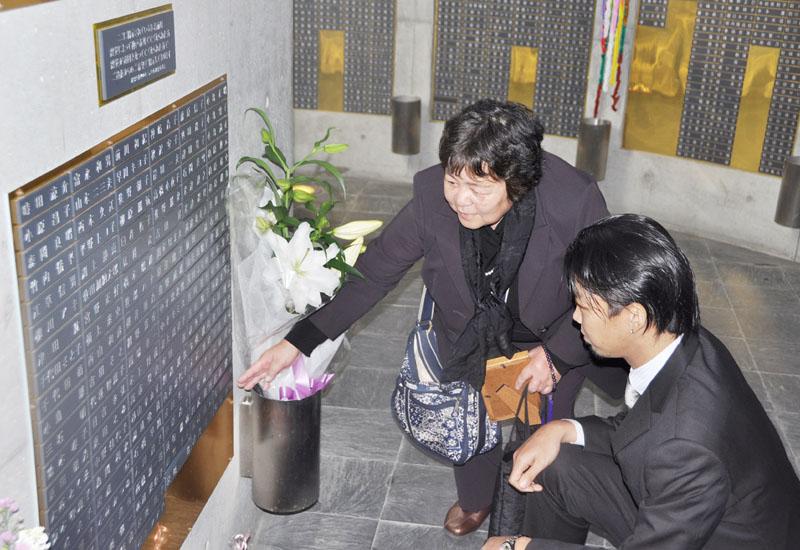 阪神大震災後に病死した保田幸子さんの名前を、モニュメントに加える姉の柳田道子さん(左)と保田さんの次男剛さん=17日、神戸市中央区