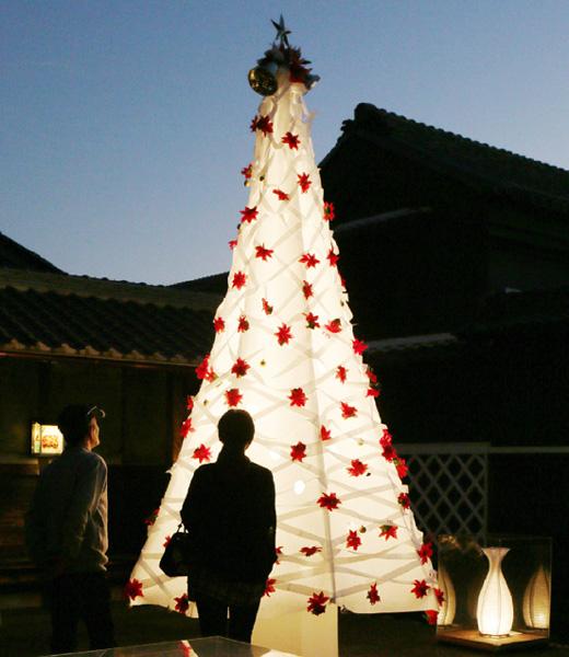夕暮れに浮かび上がる温かな和紙のツリー