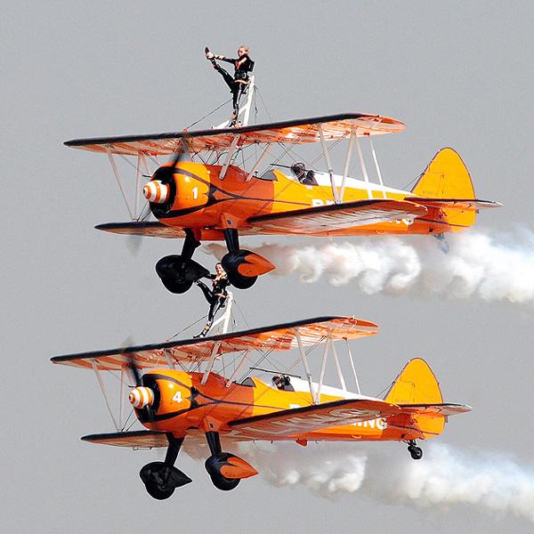 プロペラ複葉機の翼の上、何をしているの?