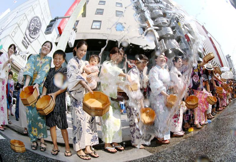 東京・銀座で、目にも涼しい浴衣で打ち水